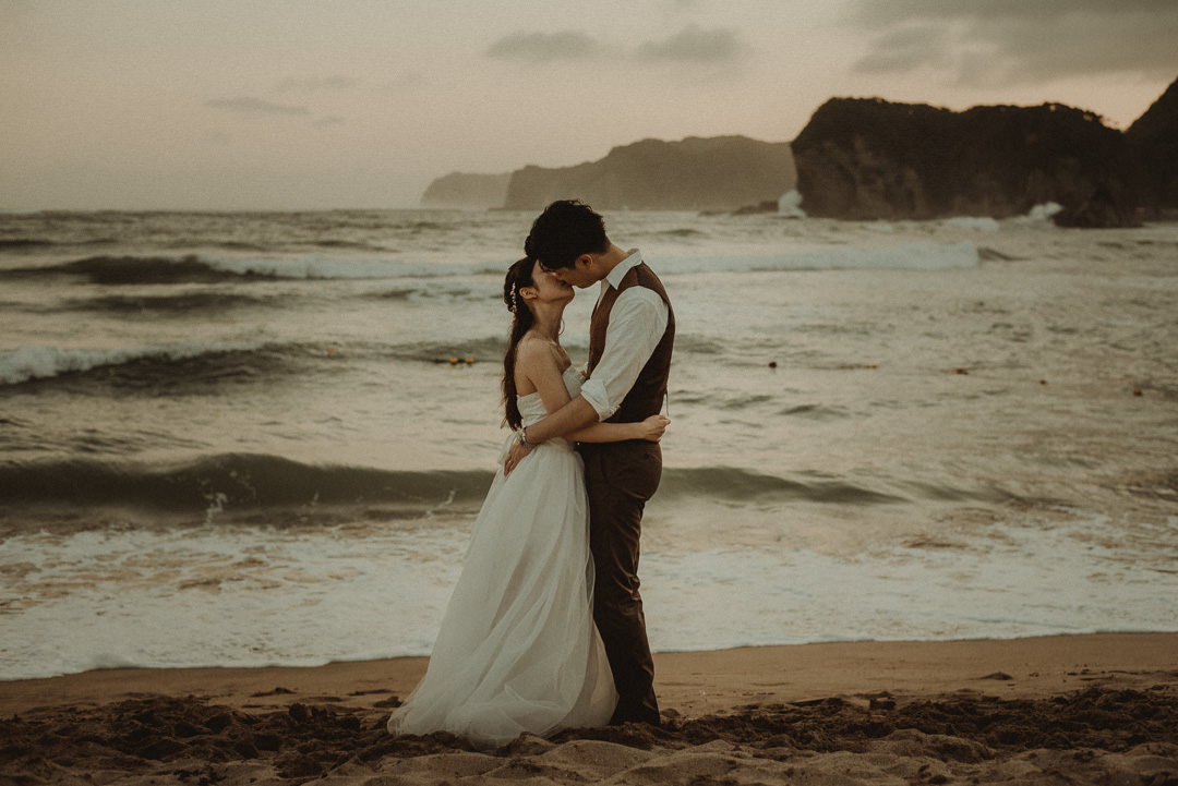 Japan elopement on the beach and waves at the sea and cliffs in a distance.